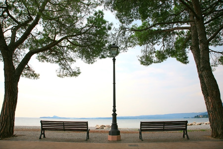 maderno: View of Lake Garda in Italy framed with trees and benches Stock Photo