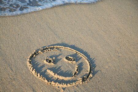 ビーチの砂の中を描く笑顔