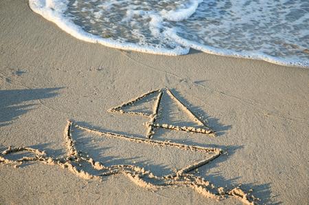 ビーチの砂の中を描くヨット 写真素材