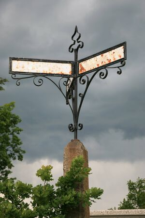 moody: Antique rusty signpost and moody sky Stock Photo