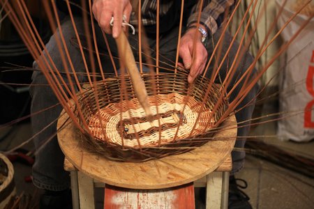 basketry: Hands of an old craftsman working on a wicker basket Stock Photo