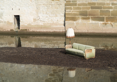 Flood desaster with furniture on an island in the water 写真素材