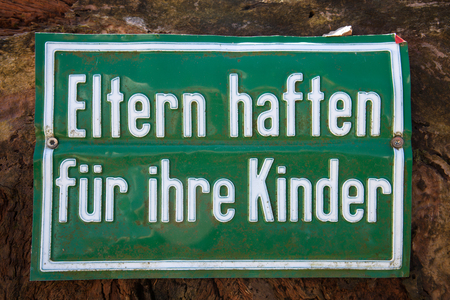 German warning sign at a construction site Eltern haften fuer ihre Kinder translates into Parents are liable for their children in English language Stock Photo