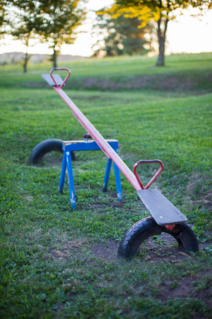 Old empty metal seesaw in an outdoor children's playground 免版税图像