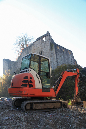 Small excavator on a consruction site hill in front of an ancient castle ruin