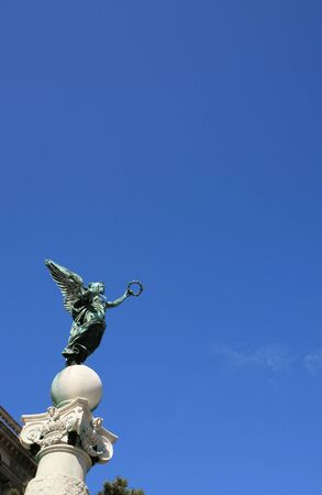 Top column statue of an angel with wings and wreath in Vienna in Austria at blue sky background