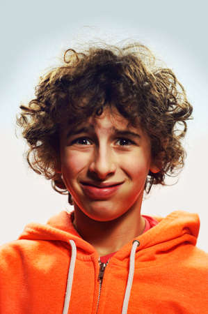A young portrait of a boy with a funny cheeky face