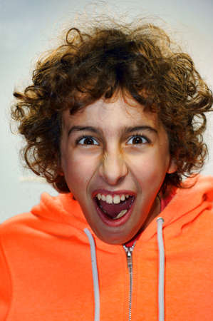 mockery: A young boy portrait  with his open mouth in a funny gesture