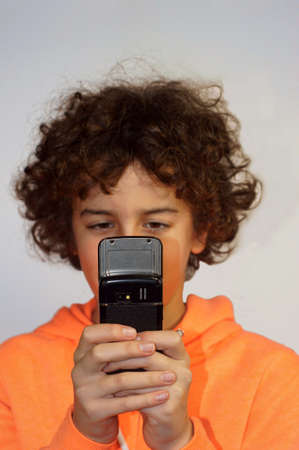 A boy is playing with his mobile phone             photo