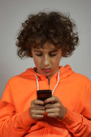 A boy is sending a message on his mobile phone       photo