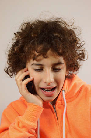 A young boy is talking on a mobile phone                photo