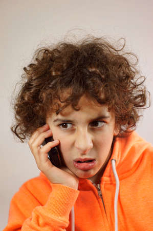 mockery: A young boy is talking on the phone with a mockery gesture
