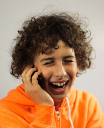 A young boy is chatting with his friends and laughing on a mobile phone                       photo
