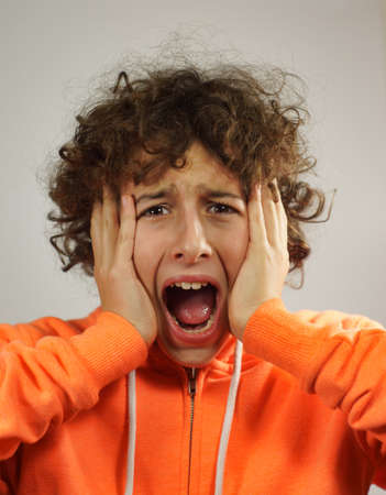 A young boy is screaming by holding his head between his hands