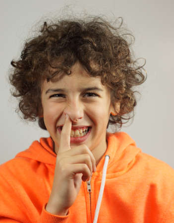 A young boy is picking his nose with a cheeky smile                    Stock Photo