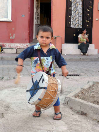 Little gypsy musician plays drum