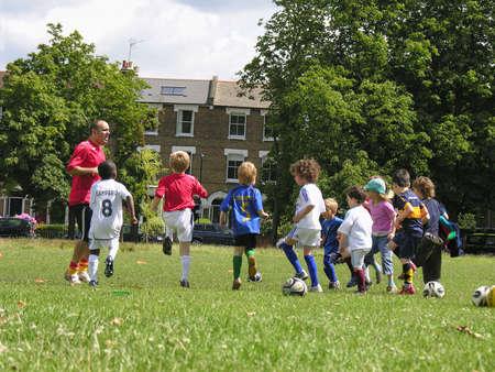 Little kids on football training in the park