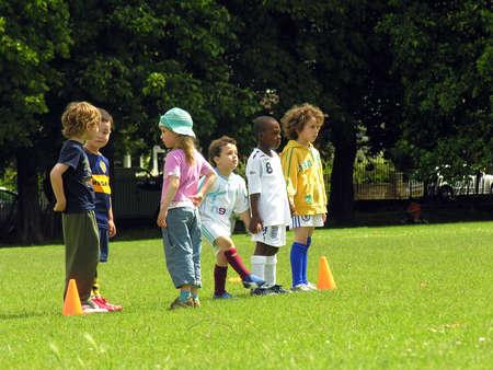Kids play football in the park Publikacyjne