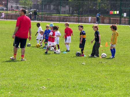life coaching: Kids playing football in the park Editorial