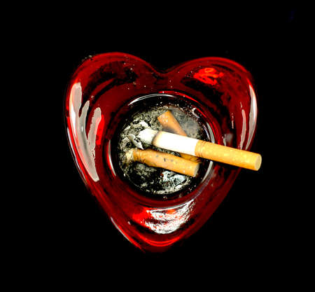 Cigarette butts in a heart shaped ashtray Imagens