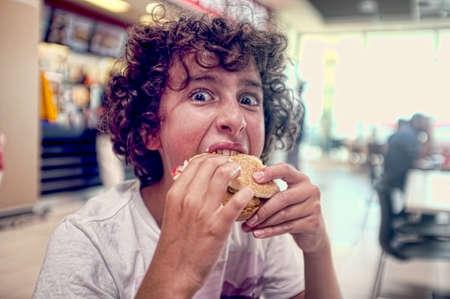 Teen boy bites his burger Stock Photo