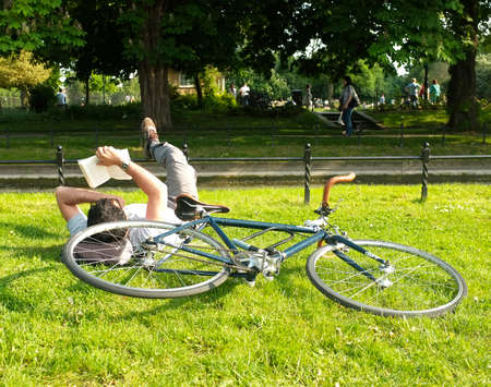 Man reads a book on the grass next to his bicycle in Clissold Park London