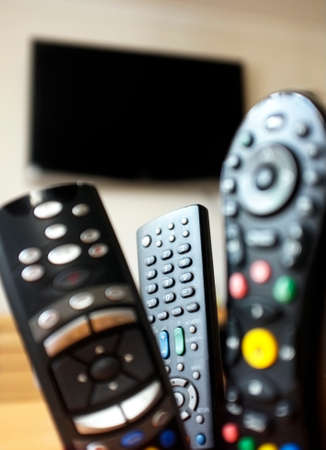 Group of TV remote controls with a TV at the background