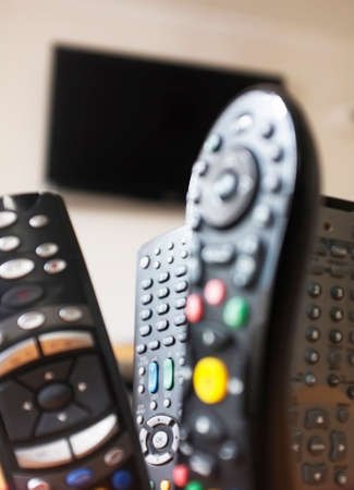 remote controls: Group of TV remote controls with a TV at the background