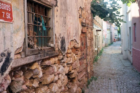 damaged houses: Narrow road between old damaged stone houses