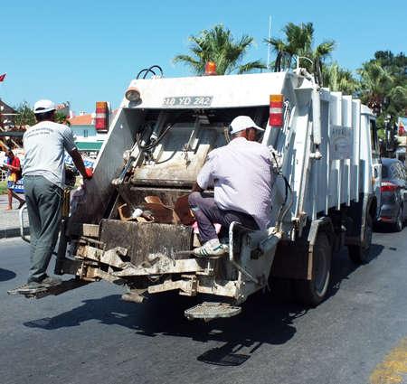 Garbage men behind the garbage truck Éditoriale