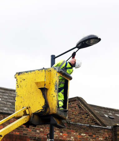Council worker painting the street lamp