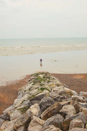 wide  wet: People walk on wide wet beach after the tide i