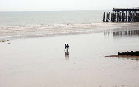 wide  wet: People walk on wide wet beach after the tide Stock Photo
