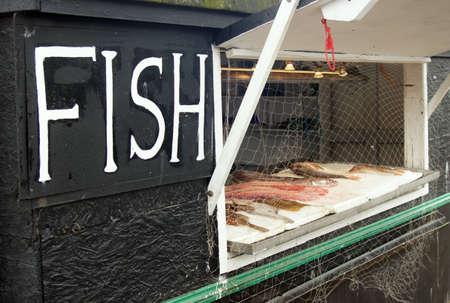 fish vendor: Small fish vendor with fresh raw fish display
