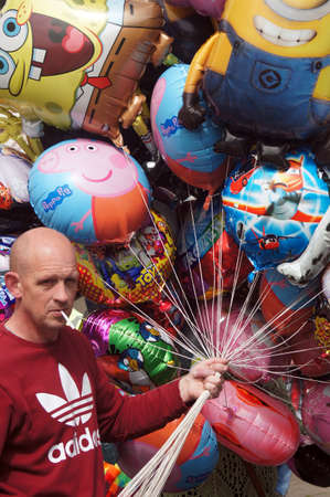 hastings: Balloon seller holding colorful balloons