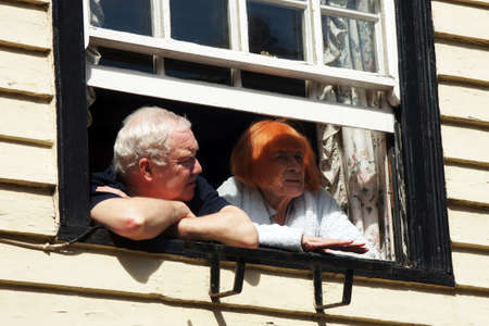 parade of homes: Elderly couple look out from their window Editorial