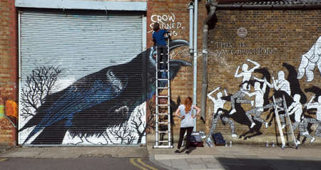 Graffiti artists paints the building wall Editorial