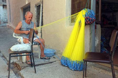 fishnet: Elderly fisherman mending his fishnet