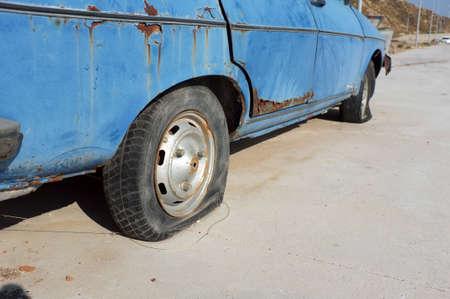 abandoned car: Flat tire of abandoned car