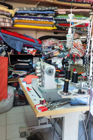 maquinas de coser: Traditional tailor workshop with sewing machines and fabrics