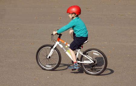 casco rojo: El muchacho joven con el ciclismo casco rojo