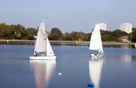 dinghies: People sail on the reservoir surrounded by the buildings