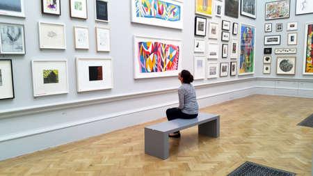 로얄 아카데미의 예술 작품을 보는 미술 애호가