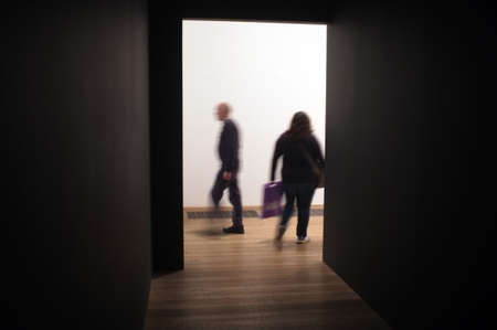 conceptional: People pass as silhouettes at the entrance of the dark corridor in Tate Modern, London