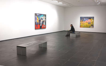 viewing: Art lover sits and views an artwork in a gallery in Ghent, Belgium