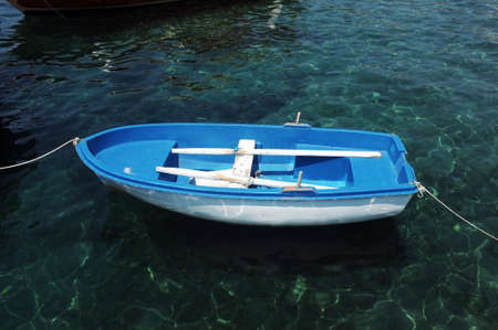 Blue small boat floating on water Stock Photo