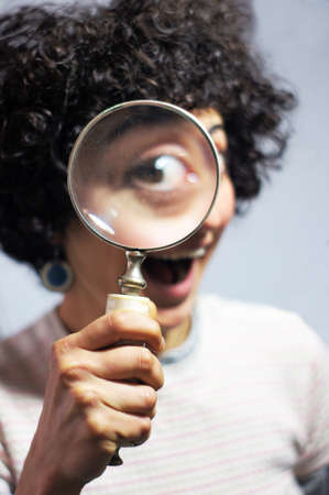 Woman holding and looking through a magnifier Stok Fotoğraf - 99154024