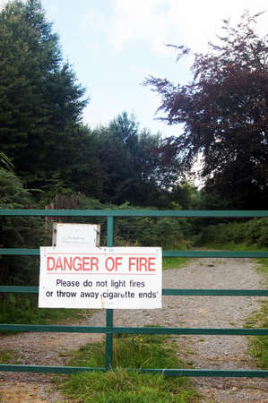 Warning sign on metal gate in woodland