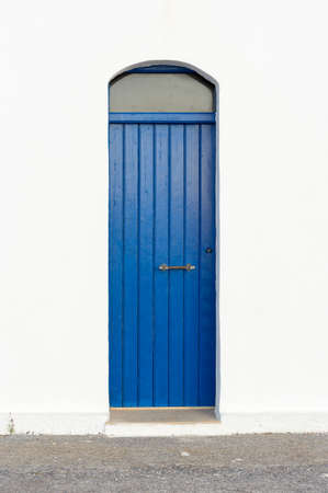 Blue narrow timber door in the white wall of the church photo