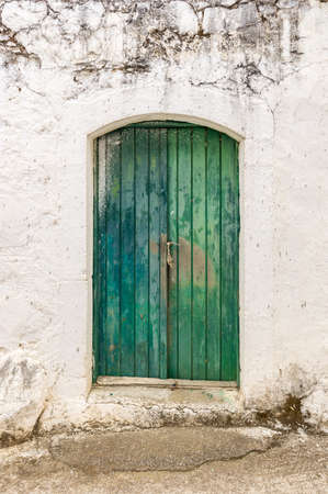 dingy: Old green timber door in the scuffed wall rural scenery Stock Photo